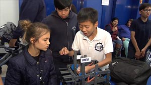 Three students work together on a robot